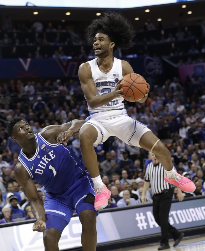 North Carolina's Coby White (2) drives to the basket against Duke's Zion Williamson (1) during the second half of an NCAA college basketball game in the Atlantic Coast Conference tournament in Charlotte, N. (AP Photo/Chuck Burton)