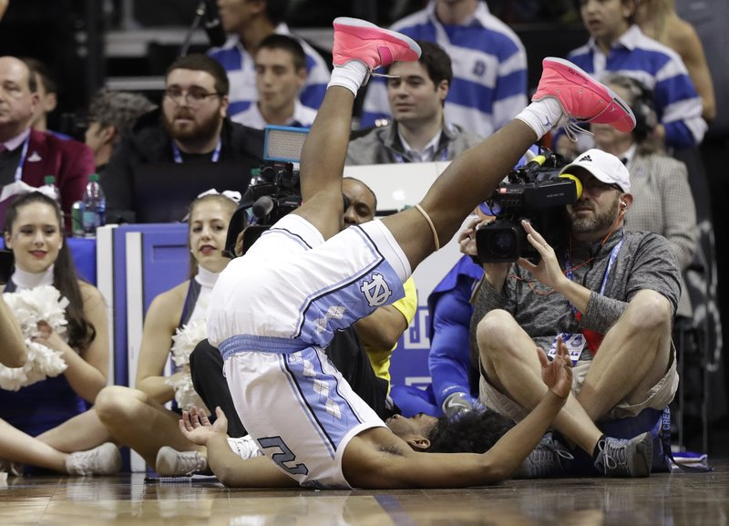 North Carolina's Coby White (2) flips over after chasing a loose ball against Duke during the first half of an NCAA college basketball game in the Atlantic Coast Conference tournament in Charlotte, N. (AP Photo/Chuck Burton)
