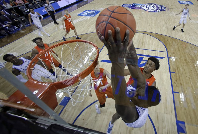 Duke's Zion Williamson, right, dunks against Syracuse during the second half of an NCAA college basketball game in the Atlantic Coast Conference tournament in Charlotte, N. (AP Photo/Chuck Burton)