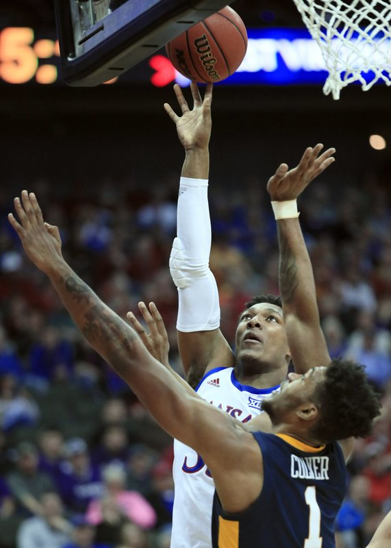 Kansas forward David McCormack (33) shoots over West Virginia forward Derek Culver (1) during the first half of an NCAA college basketball game in the semifinals of the Big 12 conference tournament in Kansas City, Mo. (AP Photo/Orlin Wagner)
