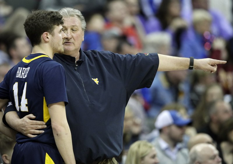 West Virginia head coach Bob Huggins talks with guard Chase Harler (14) during the first half of an NCAA college basketball game in the semifinals of the Big 12 conference tournament in Kansas City, Mo. (AP Photo/Orlin Wagner)