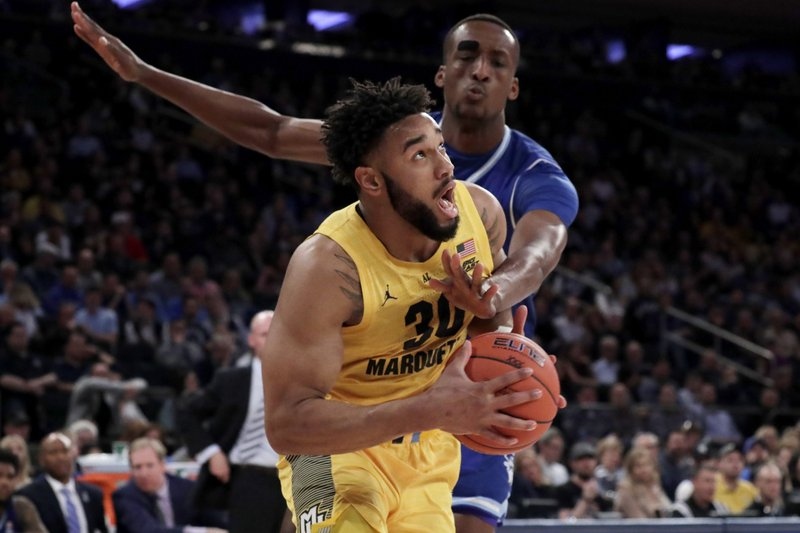 Marquette forward Ed Morrow (30) drives against Seton Hall center Romaro Gill (35) during the first half of an NCAA college basketball semifinal game in the Big East men's tournament, Friday, March 15, 2019, in New York. (AP Photo/Julio Cortez)