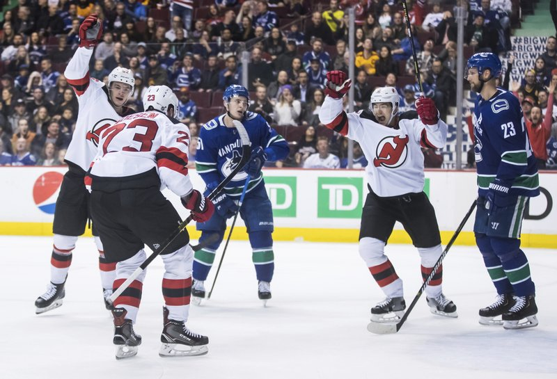 New Jersey Devils' Stefan Noesen (23), Blake Pietila, back left, and Connor Carrick, second from right, celebrate Noesen's goal as Vancouver Canucks' Troy Stecher, third left, and Alexander Edler, right, of Sweden, react during the third period of an NHL hockey game Friday, March 15, 2019, in Vancouver, British Columbia. (Darryl Dyck/The Canadian Press via AP)