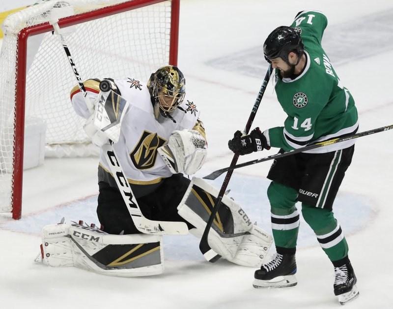 Vegas Golden Knights goaltender Marc-Andre Fleury (29) deflects a shot with his glove under pressure from Dallas Stars left wing Jamie Benn (14) in the third period of an NHL hockey game in Dallas, Friday, March 15, 2019. (AP Photo/Tony Gutierrez)