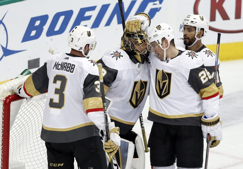Vegas Golden Knights' Brayden McNabb (3), Paul Stastny (26) and Pierre-Edouard Bellemare, rear, celebrate with goalie Marc-Andre Fleury, second from left, after their 2-1 win against the Dallas Stars in an NHL hockey game in Dallas, Friday, March 15, 2019. (AP Photo/Tony Gutierrez)