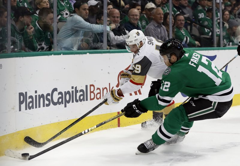 Vegas Golden Knights right wing Reilly Smith (19) and Dallas Stars center Radek Faksa (12) compete for control of the puck in the first period of an NHL hockey game in Dallas, Friday, March 15, 2019. (AP Photo/Tony Gutierrez)