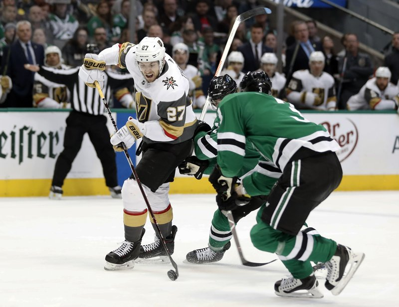 Vegas Golden Knights defenseman Shea Theodore (27) works to reach the net for a shot as Dallas Stars' Andrew Cogliano, rear, and John Klingberg (3) defend in the second period of an NHL hockey game in Dallas, Friday, March 15, 2019. (AP Photo/Tony Gutierrez)
