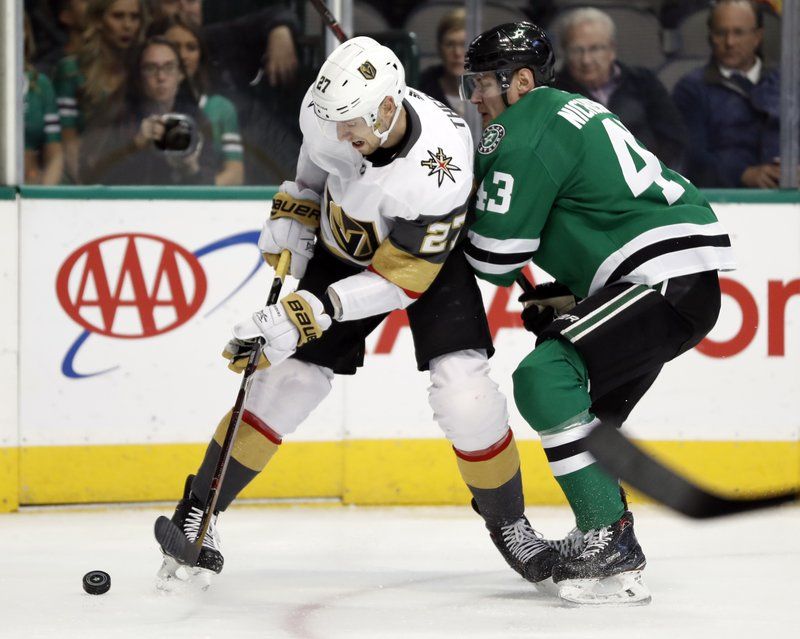 Vegas Golden Knights defenseman Shea Theodore (27) and Dallas Stars right wing Valeri Nichushkin (43) work to control a puck in the first period of an NHL hockey game in Dallas, Friday, March 15, 2019. (AP Photo/Tony Gutierrez)