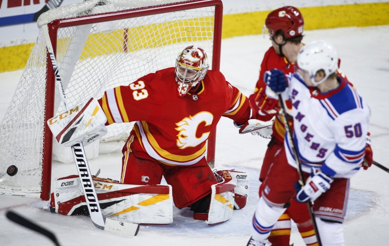 New York Rangers' Lias Andersson, right, looks on as Calgary Flames goalie David Rittich defelects shot during the second period of an NHL hockey game in Calgary, Alberta, Friday, March 15, 2019. (Jeff McIntosh/The Canadian Press via AP)