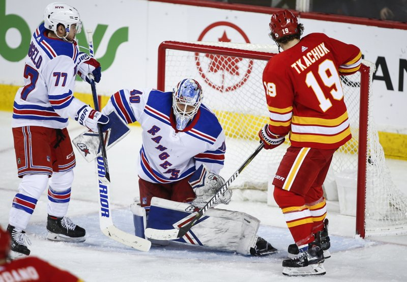 New York Rangers goalie Alexandar Georgiev, center, lets in a goal frbym Calgary Flames' Matthew Tkachuk during the second period of an NHL hockey game in Calgary, Alberta, Friday, March 15, 2019. (Jeff McIntosh/The Canadian Press via AP)