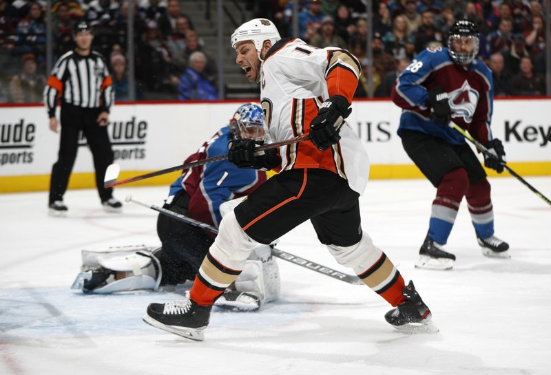 Anaheim Ducks center Ryan Getzlaf, front, pursues the puck as Colorado Avalanche goaltender Semyon Varlamov looks for it during the second period of an NHL hockey game Friday, March 15, 2019, in Denver. (AP Photo/David Zalubowski)