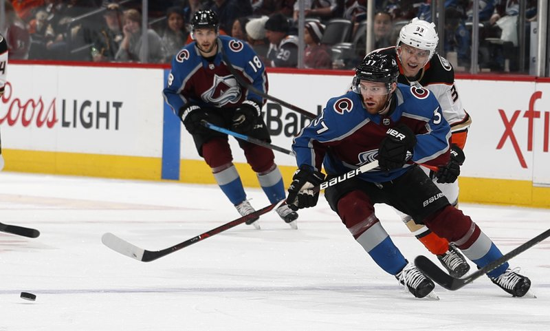 Colorado Avalanche left wing J.T. Compher, front, pursues the puck with Anaheim Ducks right wing Jakob Silfverberg during the first period of an NHL hockey game Friday, March 15, 2019, in Denver. (AP Photo/David Zalubowski)
