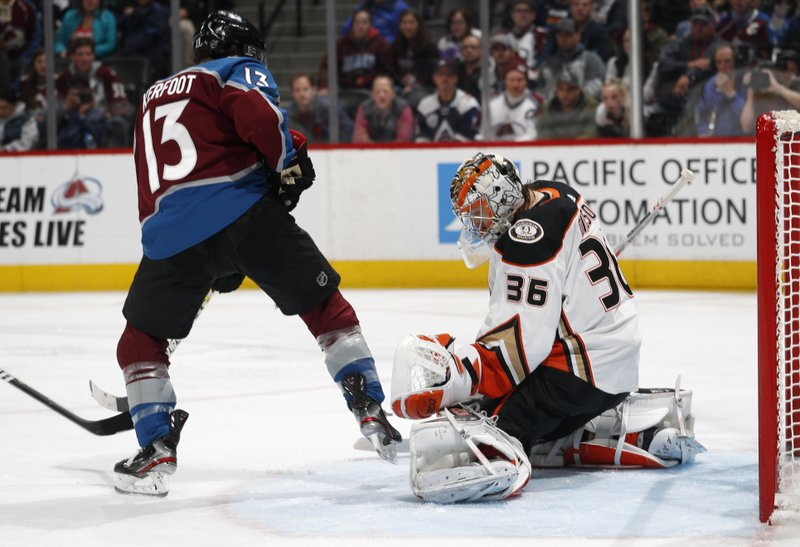 Anaheim Ducks goaltender John Gibson, right, makes a glove save against Colorado Avalanche center Alexander Kerfoot during the third period of an NHL hockey game Friday, March 15, 2019, in Denver. (AP Photo/David Zalubowski)