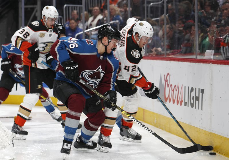 Colorado Avalanche right wing Mikko Rantanen, front left, fights for control of the puck with Anaheim Ducks defenseman Josh Manson, front right, as center Derek Grant trails the play during the third period of an NHL hockey game Friday, March 15, 2019, in Denver. (AP Photo/David Zalubowski)