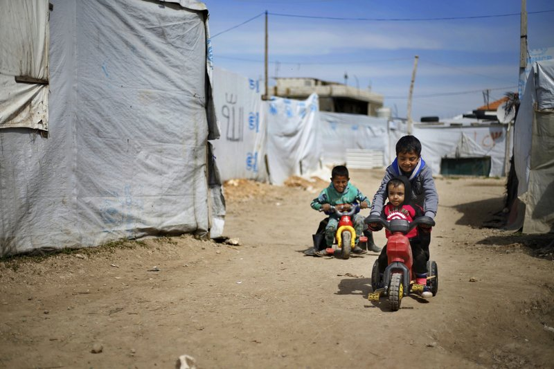 This Tuesday, March 12, 2019 photo, Syrian displaced children play outside their family tents at a Syrian refugee camp in the town of Bar Elias, in Lebanon's Bekaa Valley. (AP Photo/Bilal Hussein)