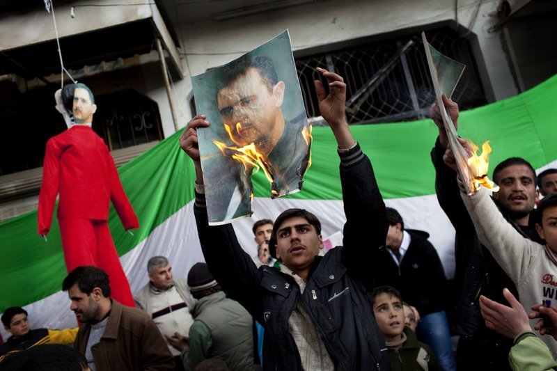 FILE - In this Feb. 26, 2012 file photo, people burn portraits of Syrian President Bashar Al-Assad during a demonstration on the outskirts of Idlib, northern Syria. (AP Photo/Rodrigo Abd, File)
