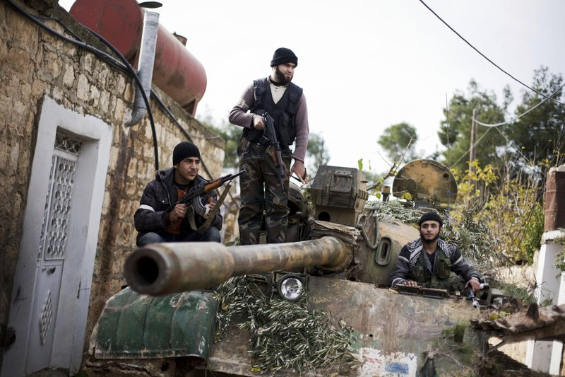 ADVANCE FOR PUBLICATION ON FRIDAY, MAR. 15, AND THEREAFTER - FILE - In this Dec 12, 2012 file photo, Kurdish opposition fighters man a tank stolen from the Syrian Army, in Fafeen village, north of Aleppo province, Syria. (AP Photo/Manu Brabo, File)