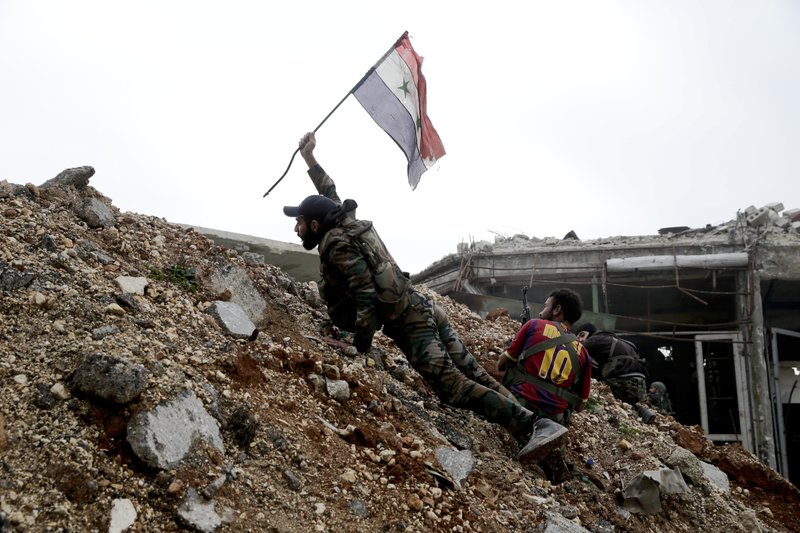 FILE - In this Dec. 5, 2016 file photo, a Syrian army soldier places a Syrian national flag during a battle with rebel fighters at the Ramouseh front line, east of Aleppo, Syria. (AP Photo/Hassan Ammar)