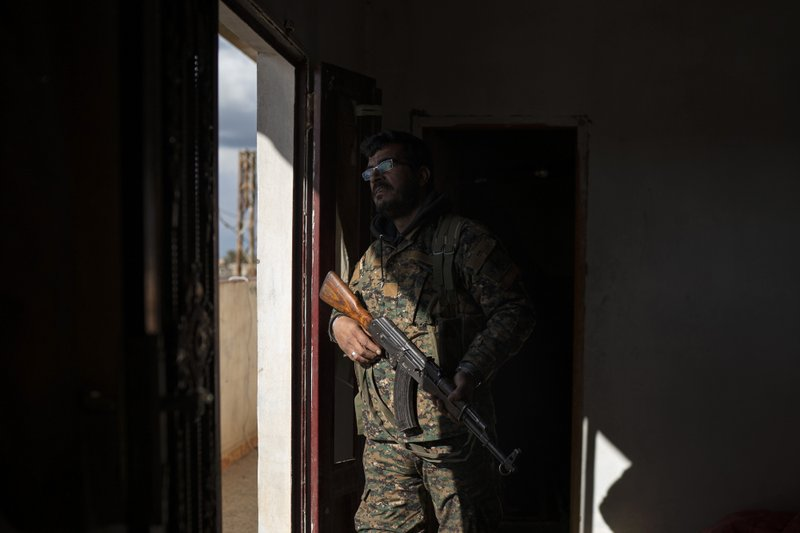 FILE - In this Feb. 17, 2019 file photo, Dia Hassakeh, 45, a fighter in the Kurdish-led U.S-backed Syrian Democratic Forces, looks out of a building in Baghouz, Syria. (AP Photo/Felipe Dana, File)