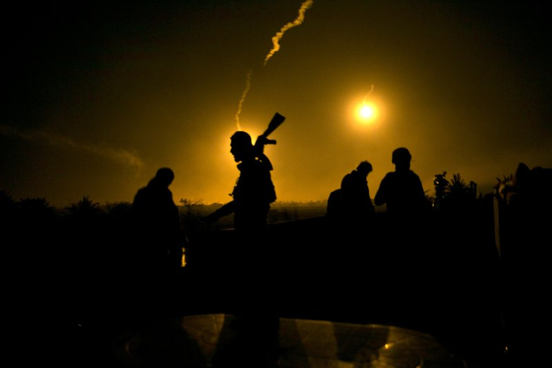 FILE - In this Tuesday, March 12, 2019 file photo, a U.S.-backed Syrian Democratic Forces (SDF) fighter watches illumination rounds light up Baghouz, Syria, as the last pocket of Islamic State militants is attacked. (AP Photo/Maya Alleruzzo, File)