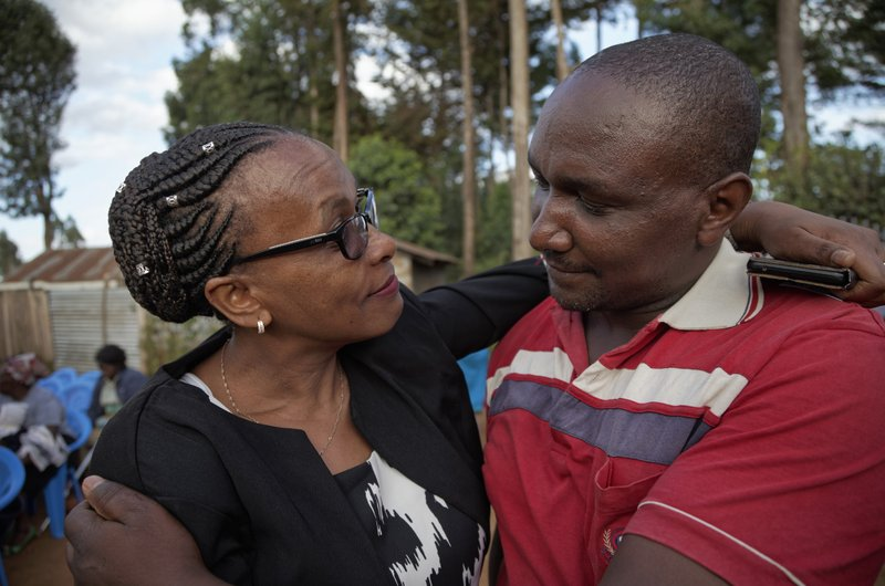 In this photo taken Thursday, March 14, 2019, sister Goreti Kimani consoles brother Chira Kageche at a prayers ceremony for their brother Catholic priest Rev. (AP Photo/Sayyid Abdul Azim)