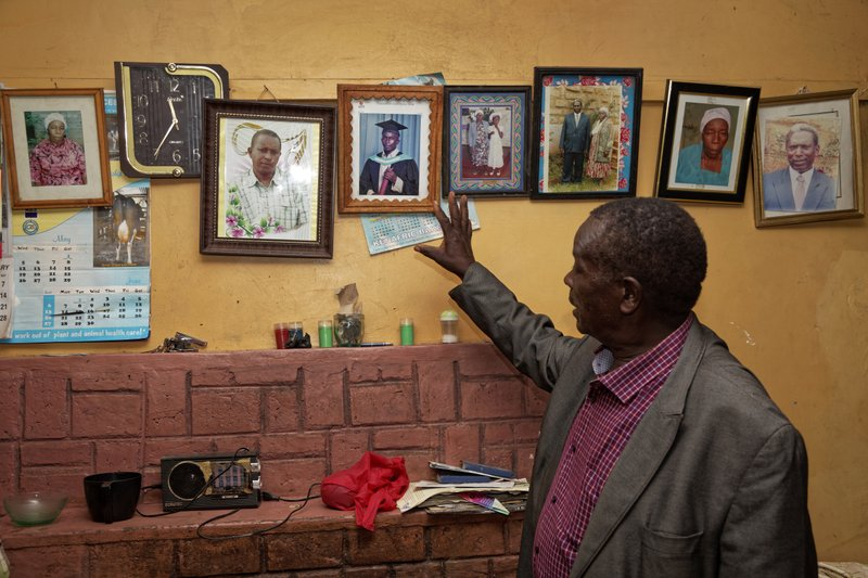 In this photo taken Thursday, March 14, 2019, George Mukua, the cousin of Catholic priest Rev. George Mukua Kageche, 40, who died in the plane crash in Ethiopia, points to a photograph of the priest taken in 2006 at his first graduation ceremony, after a prayers ceremony held at his home in Githunguri, near Nairobi, in Kenya. (AP Photo/Sayyid Abdul Azim)