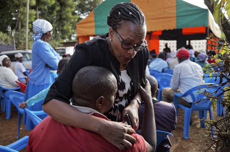 In this photo taken Thursday, March 14, 2019, sister Goreti Kimani consoles brother Chira Kageche at a memorial service for their brother, Catholic priest Rev. (AP Photo/Sayyid Abdul Azim)