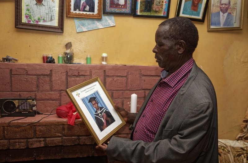 In this photo taken Thursday, March 14, 2019, George Mukua, the cousin of Catholic priest Rev. George Mukua Kageche, 40, who died in the recent plane crash in Ethiopia, points to a photograph of the priest taken in 2007 at his second graduation ceremony, after a prayers ceremony held at his home in Githunguri, near Nairobi, in Kenya. (AP Photo/Sayyid Abdul Azim)