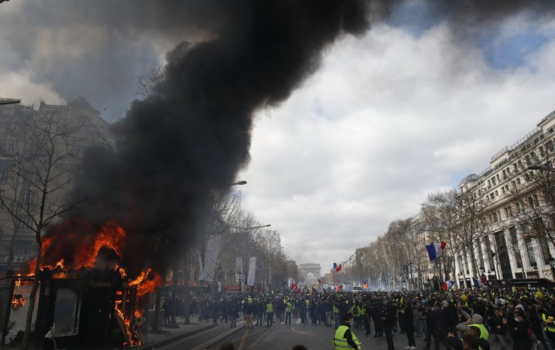 A news stand burns during a yellow vests demonstration on the Champs Elysees avenue Saturday, March 16, 2019 in Paris. (AP Photo/Christophe Ena)