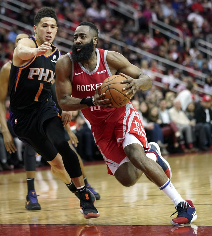 Houston Rockets' James Harden (13) drives toward the basket as Phoenix Suns' Devin Booker (1) defends during the second half of an NBA basketball game Friday, March 15, 2019, in Houston. (AP Photo/David J. Phillip)