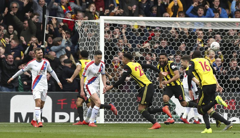 Watford's Etienne Capoue, centre, celebrates scoring his side's first goal of the game, during the FA Cup quarter final soccer match between Watford and Crystal Palace , at Vicarage Road, in Watford, England, Saturday March 16, 2019. (Jonathan Brady/PA via AP)