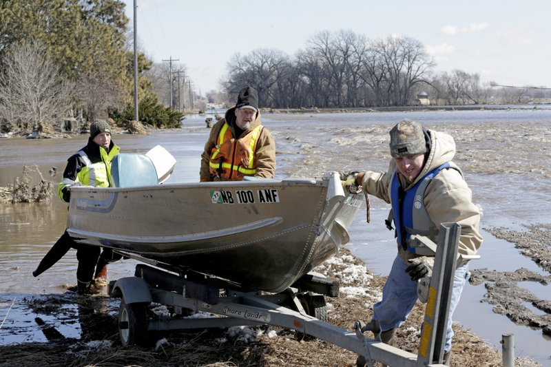 RETRANSMISSION TO CORRECT SURNAME - Tom Wilke, center, his son Chad, right, and Nick Kenny, load a boat out of the swollen waters of the North Fork of the Elkhorn River after checking on the Witke's flooded property, in Norfolk, Neb. (AP Photo/Nati Harnik)