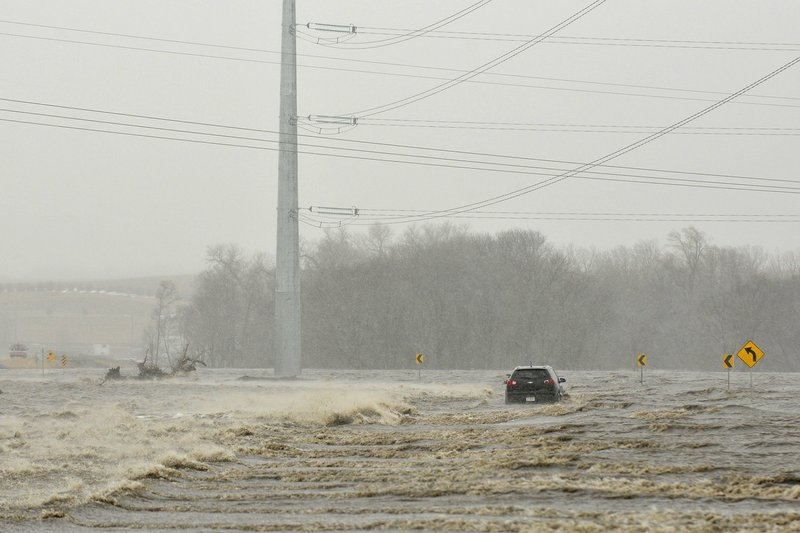In this March 14, 2019 photo an abandoned car sits on Industrial Highway in flood waters north of Norfolk, Neb. (Darin Epperly/Norfolk Daily News via AP)