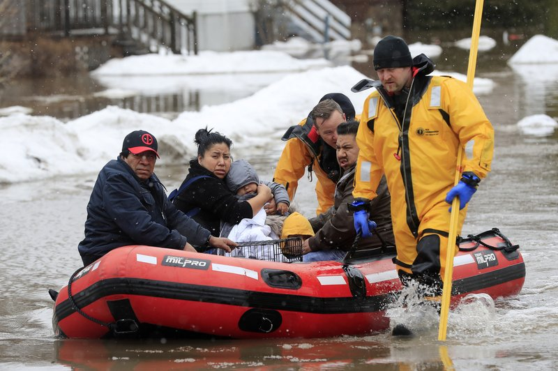 Green Bay firefighters assist residents in evacuating their homes due to the East river flooding on Friday, March 15, 2019 in Green Bay, Wis. (Adam Wesley/The Post-Crescent via AP)