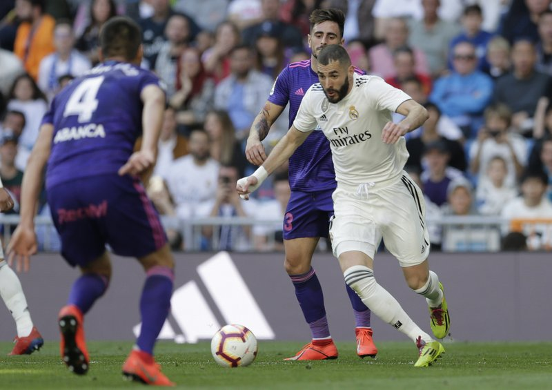 Real Madrid's Karim Benzem, right, controls the ball during a Spanish La Liga soccer match between Real Madrid and Celta at the Santiago Bernabeu stadium in Madrid, Spain, Saturday, March 16, 2019. (AP Photo/Paul White)
