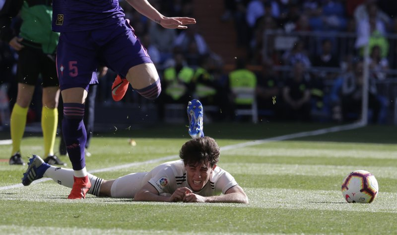 Real Madrid's Alvaro Odriozola, right, is tackled by Celta's Okay Yokuslu during a Spanish La Liga soccer match between Real Madrid and Celta at the Santiago Bernabeu stadium in Madrid, Spain, Saturday, March 16, 2019.(AP Photo/Paul White)