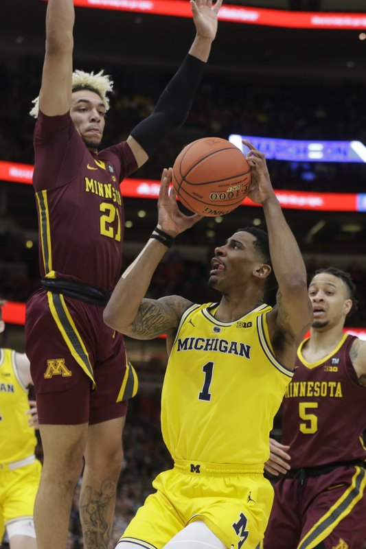 Michigan's Charles Matthews (1) drives against Minnesota's Jarvis Omersa (21) during the first half of an NCAA college basketball game in the semifinals of the Big Ten Conference tournament, Saturday, March 16, 2019, in Chicago. (AP Photo/Kiichiro Sato)