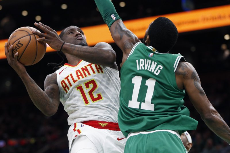 Atlanta Hawks' Taurean Prince (12) shoots against Boston Celtics' Kyrie Irving (11) during the second half of an NBA basketball game in Boston, Saturday, March 16, 2019. (AP Photo/Michael Dwyer)