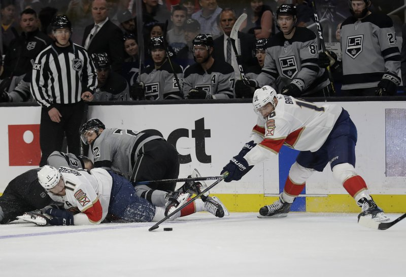 Florida Panthers' Jonathan Huberdeau (11) and Aleksander Barkov, right, get tangled with Los Angeles Kings' Trevor Lewis, center, during the third period of an NHL hockey game Saturday, March 16, 2019, in Los Angeles. (AP Photo/Marcio Jose Sanchez)