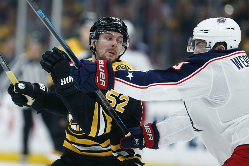 Columbus Blue Jackets' Zach Werenski, right, checks Boston Bruins' Sean Kuraly (52) during the second period of an NHL hockey game in Boston, Saturday, March 16, 2019. (AP Photo/Michael Dwyer)
