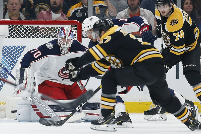 Boston Bruins' Patrice Bergeron, foreground, scores on Columbus Blue Jackets' Joonas Korpisalo (70) during the first period of an NHL hockey game in Boston, Saturday, March 16, 2019. (AP Photo/Michael Dwyer)