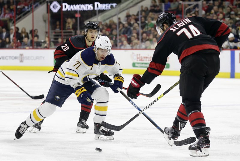 Buffalo Sabres' Evan Rodrigues (71) skates between Carolina Hurricanes' Sebastian Aho (20), of Finland, and Jaccob Slavin (74) during the first period of an NHL hockey game in Raleigh, N. (AP Photo/Gerry Broome)