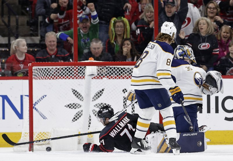 Carolina Hurricanes' Lucas Wallmark (71), of Sweden, scores against Buffalo Sabres goalie Linus Ullmark (35), of Sweden, during the first period of an NHL hockey game in Raleigh, N. (8) looks on. (AP Photo/Gerry Broome)