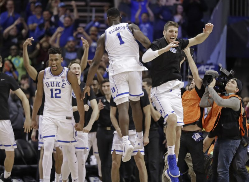 Duke players including Javin DeLaurier (12) and Zion Williamson (1) celebrate after defeating Florida State in the NCAA college basketball championship game of the Atlantic Coast Conference tournament in Charlotte, N. (AP Photo/Chuck Burton)