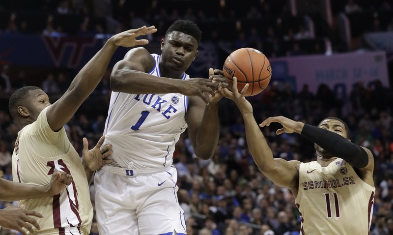 Duke's Zion Williamson, center, loses the ball as he is trapped by Florida State's David Nichols, right, and Raiquan Gray, left, during the first half of the NCAA college basketball championship game of the Atlantic Coast Conference tournament in Charlotte, N. (AP Photo/Chuck Burton)