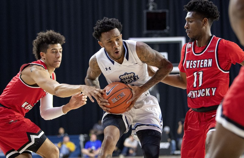 Old Dominion guard Ahmad Caver drives through the defense of Western Kentucky's Jared Savage, left, and Taveion Hollingsworth (11) during the first half of an NCAA college basketball game for the Conference USA men's tournament championship Saturday, March 16, 2019, in Frisco, Texas. (AP Photo/Jeffrey McWhorter)