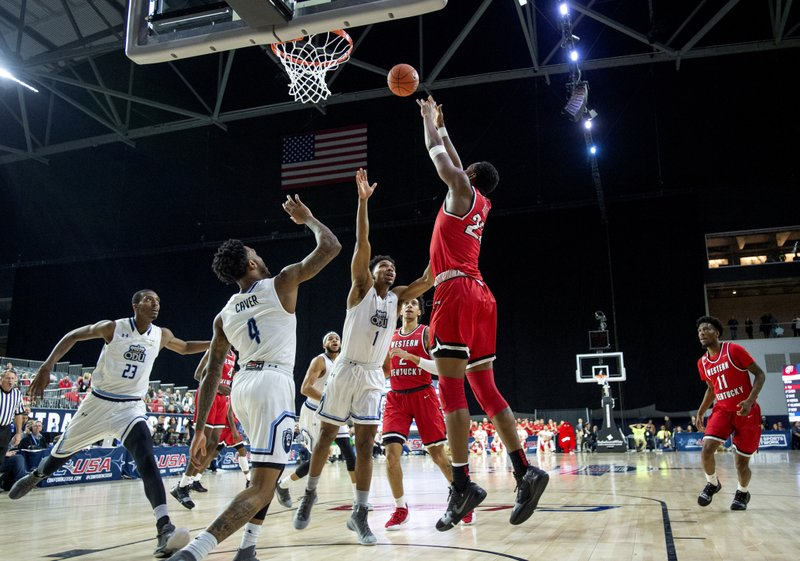 Western Kentucky center Charles Bassey (23) shoots as Old Dominion forward Dajour Dickens (23) and guards Ahmad Caver (4) and Jason Wade (1) defend during the first half of an NCAA college basketball game for the Conference USA men's tournament championship Saturday, March 16, 2019, in Frisco, Texas. (AP Photo/Jeffrey McWhorter)