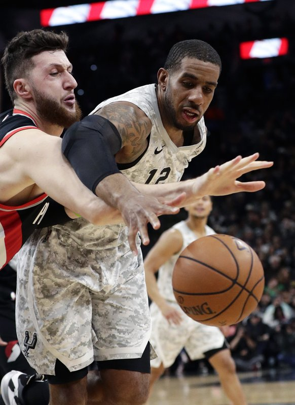 San Antonio Spurs center LaMarcus Aldridge (12) loses control of the ball as Portland Trail Blazers center Jusuf Nurkic, left, reaches in during the first half of an NBA basketball game, in San Antonio, Saturday, March 16, 2019. (AP Photo/Eric Gay)