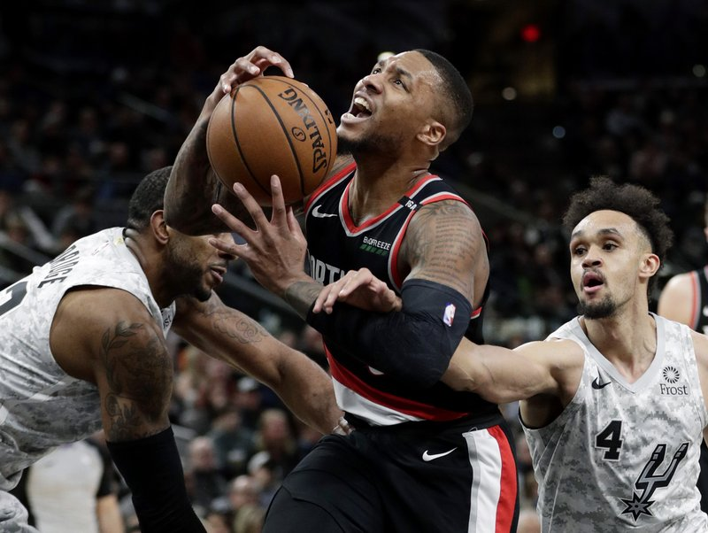 Portland Trail Blazers guard Damian Lillard (0) is fouled by San Antonio Spurs guard Derrick White (4) as he drives to the basket during the second half of an NBA basketball game in San Antonio, Saturday, March 16, 2019. (AP Photo/Eric Gay)