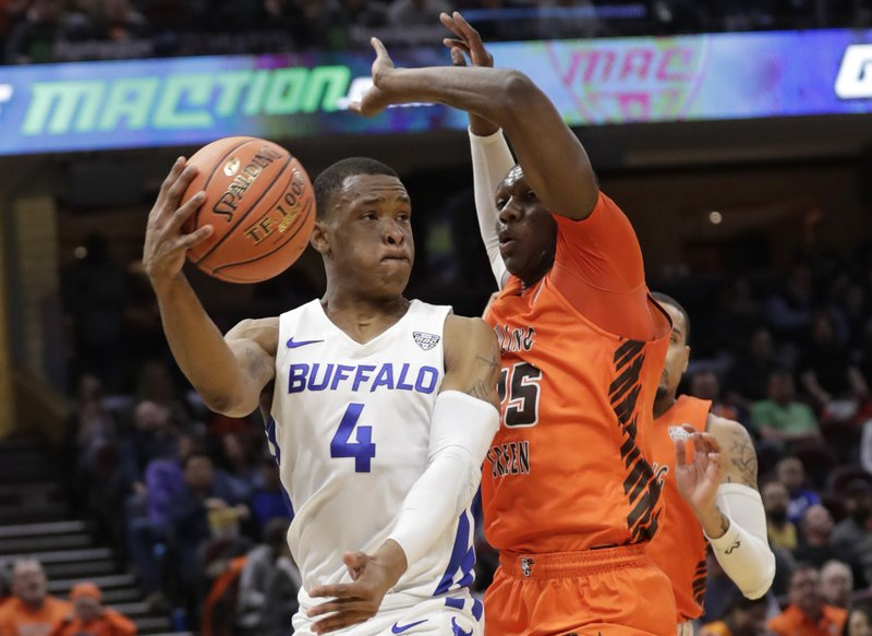 Buffalo's Davonta Jordan (4) passes against Bowling Green's Daeqwon Plowden (25) during the first half of an NCAA college basketball championship game of the Mid-American Conference men's tournament, Saturday, March 16, 2019, in Cleveland. (AP Photo/Tony Dejak)